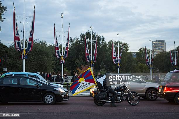 A motorcyclist drives with a Tibet flag attached to the back of his motorbike outside Buckingham Palace central London on October 20 where the...