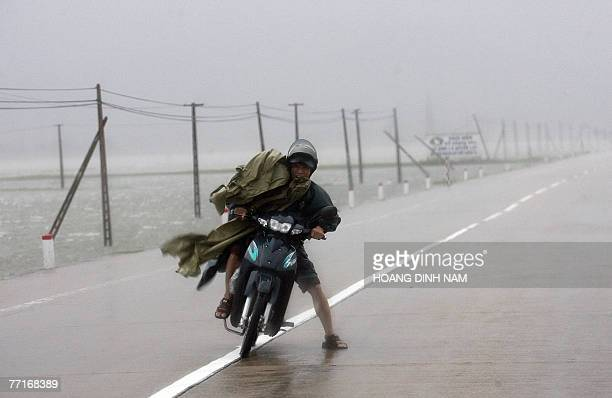 A motorcyclist fights against strong wind as he drives on national highway No 1 in the central province of Ha Tinh 03 October 2007 as tropical...