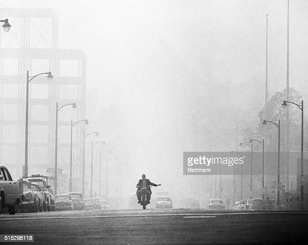 A motorcyclist in Los Angeles prepares to turn while driving along a street which is engulfed in a thick haze combined by fog and smog