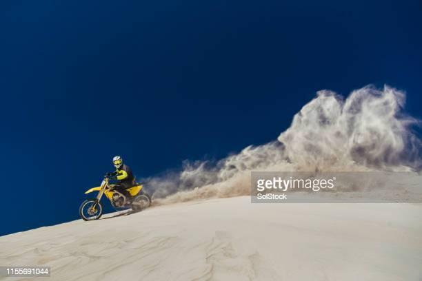 motorcyclist kicking up the sand - motocross imagens e fotografias de stock