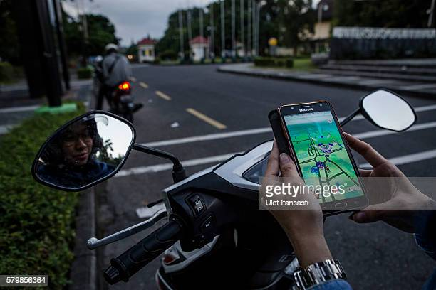 A motorcyclist Nadia plays Pokemon Go game on her smartphone on July 24 2016 in Yogyakarta Indonesia Pokemon Go which uses Google Maps and a...