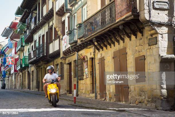 Motorcyclist on cobbled street passing medieval halftimbered architecture in Hondarribia in Basque Country Spain