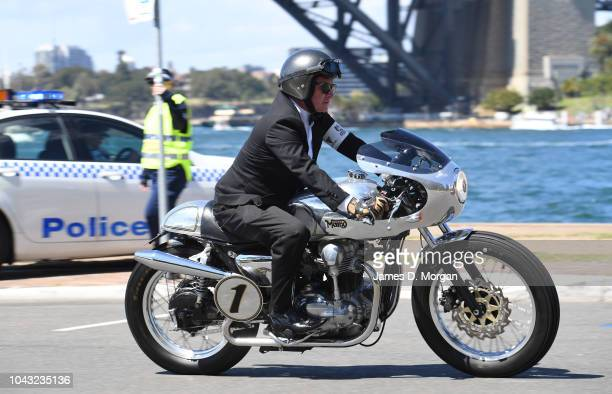 A motorcyclist passes a police officer beside the harbour during a charity ride on September 30 2018 in Sydney Australia The Distinguished...