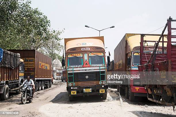 A motorcyclist passes between trucks standing idle due to a lack of qualified drivers outside the Caravan Roadways Ltd office at Sanjay Gandhi...