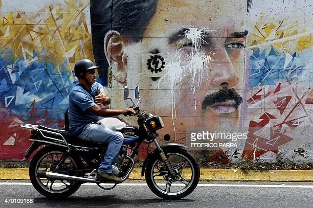 A motorcyclist passes by a graffiti depicting Venezuelan President Nicolas Maduro in Caracas on April 17 2015 AFP PHOTO/FEDERICO PARRA