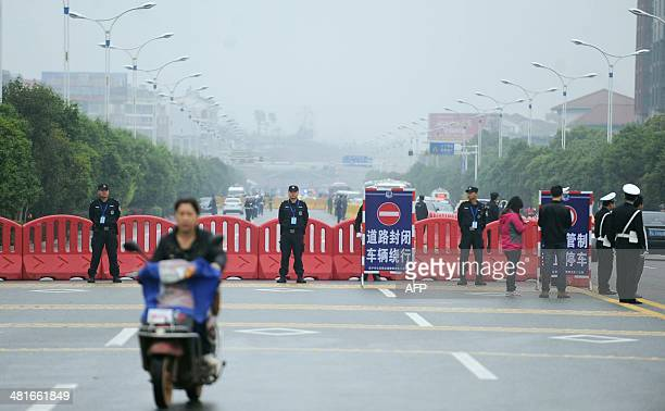 Motorcyclist passes by as police stand guard outside the Xianning Intermediate People's Court where Chinese mining tycoon Liu Han stands trial in...
