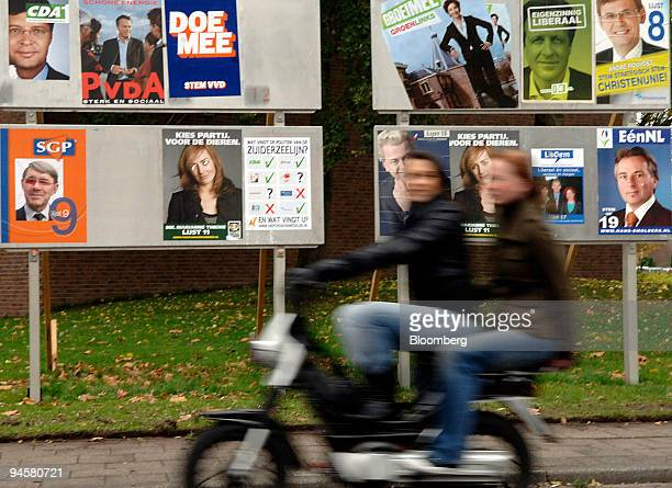 Motorcyclist passes election campaign posters in Hoogeveen, The Netherlands, on Tuesday, November 14, 2006.