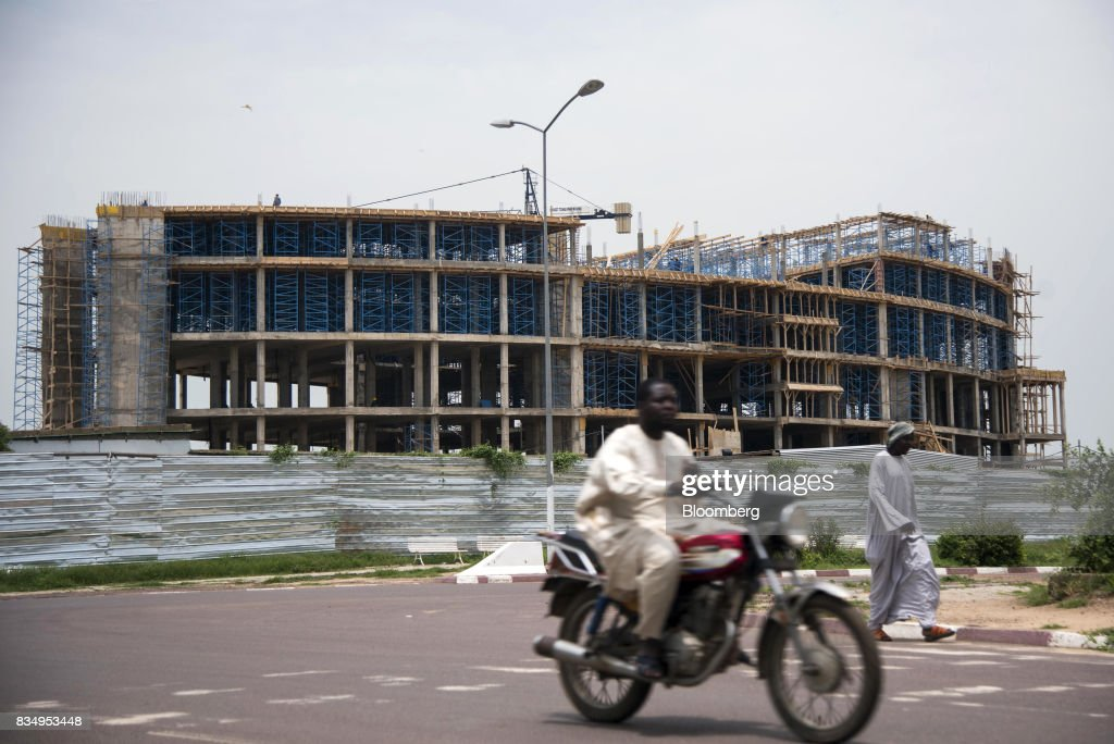 A motorcyclist passes the Cit des Affaires de N'Djamena construction site in N'Djamena, Chad, on Wednesday, Aug. 16, 2017. African Development Bank and nations signed agreement to finance a project linking the town of Ngouandere in Cameroon and Chads capital, NDjamena, according to statement handed to reporters in Cameroonian capital, Yaounde in July. Photographer: Xaume Olleros/Bloomberg via Getty Images
