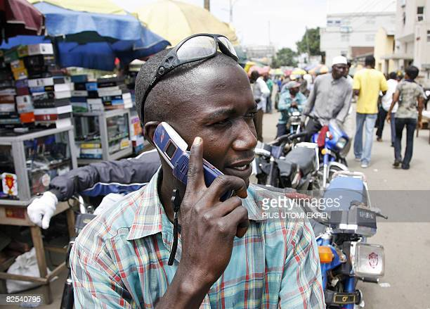 A motorcyclist phones sat on his motorbike on August 18 2008 in Obalende a district of Lagos Seven years after their launch mobile phone services...