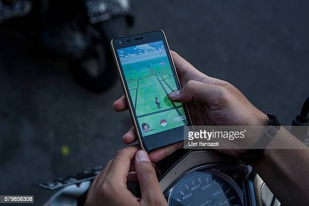 A motorcyclist plays Pokemon Go game on his smartphone on July 24 2016 in Yogyakarta Indonesia Pokemon Go which uses Google Maps and a smartphone has...