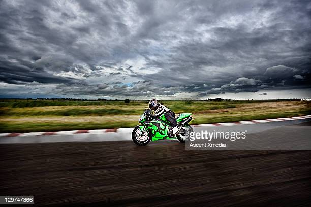 motorcyclist races around wet track on stormy day - motorcycle racing stock pictures, royalty-free photos & images