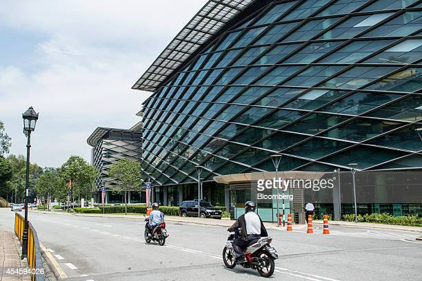 Motorcyclist ride past Sasana Kijang Bank Negara Malaysia's finance sector study center and venue for the Global Islamic Finance Forum in Kuala...