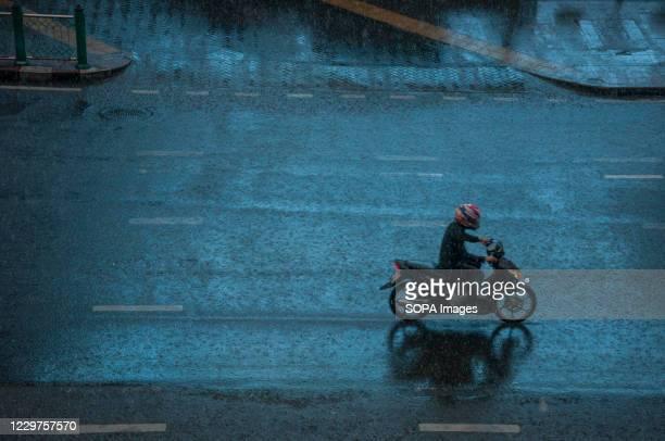 Motorcyclist rides along Ratchadamri Road on a rainy day.