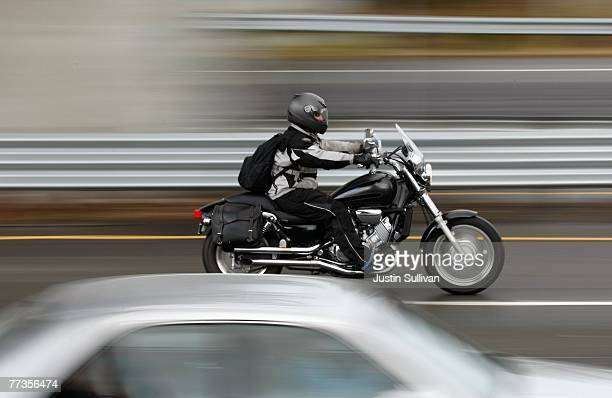 A motorcyclist rides between cars in slow moving traffic on Highway 101 October 16 2007 in Corte Madera California Motorcycle deaths are on the rise...