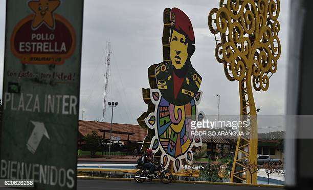 A motorcyclist rides in front of a sign depicting the late Venezuelan President Hugo Chavez in Managua on November 2 2016 Nicaragua will hold general...
