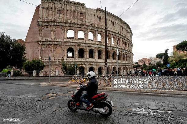 A motorcyclist rides over potholes on a road along the Colosseum in downtown Rome on April 12 2018 Romes roads problems have been existing for years...