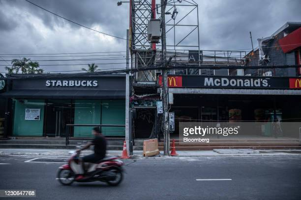 Motorcyclist rides past a closed Starbucks Corp. Coffee shop and a closed McDonald's Corp. Restaurant in Patong, Phuket, Thailand, on Saturday, Dec....