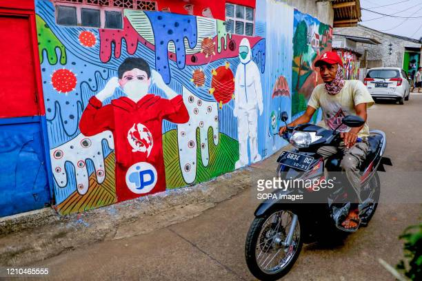Motorcyclist rides past a coronavirus awareness graffiti during a lockdown. Indonesian local artists drew murals on the walls of the houses for the...