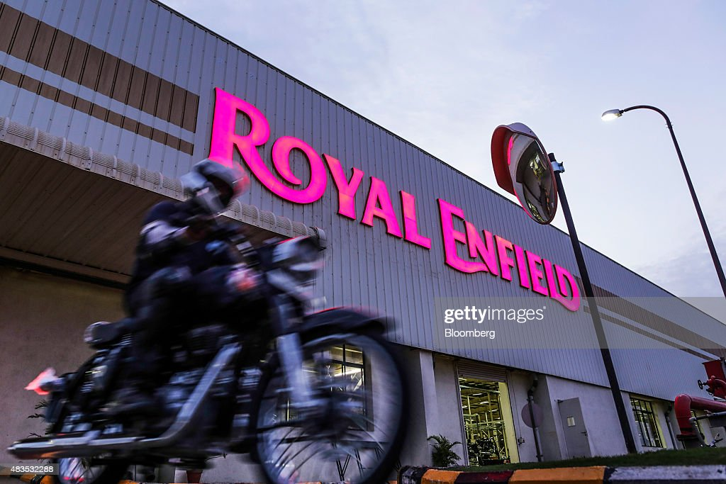 A motorcyclist rides past a Royal Enfield Motors Ltd manufacturing facility in Chennai India on Tuesday July 14 2015 In a sweltering factory in...