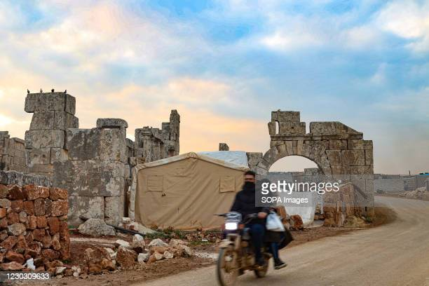 Motorcyclist rides past a tent at the Dana ancient site. A group of displaced Syrians reside inside ancient buildings dating back to the ancient...