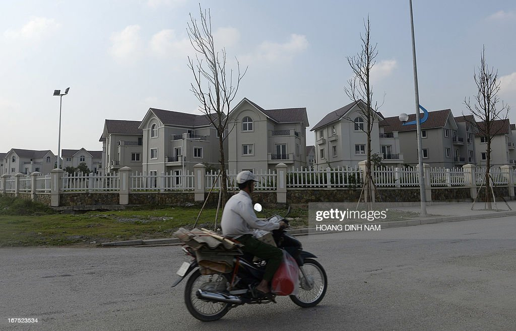 A motorcyclist rides past empty villas at a newly developed area in the suburbs of Hanoi on April 26, 2013