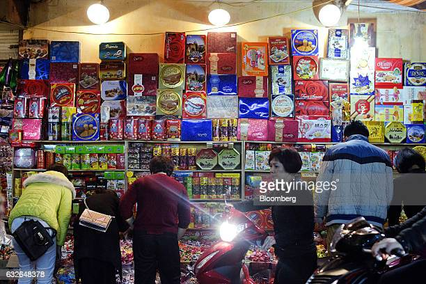A motorcyclist rides past people browsing biscuits and confectionery for sale at a street market stall ahead of the Vietnamese Lunar New Year holiday...
