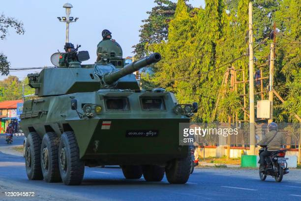 Motorcyclist rides past soldiers in a military armoured vehicle in Myitkyina, Kachin state on February 3 as Myanmar's ousted leader Aung San Suu Kyi...