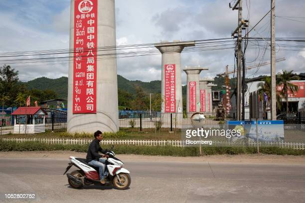 A motorcyclist rides past the construction site of the Luang Prabang railway bridge a section of the ChinaLaos Railway built by the China Railway...