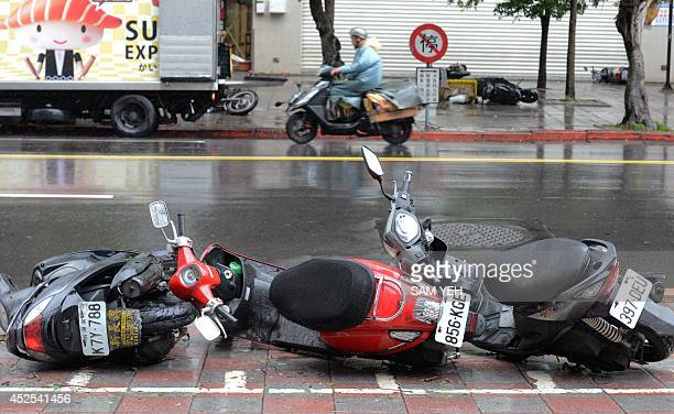 Motorcyclist rides past three downed motorcycles as Typhoon Matmo approaches Xindien district in New Taipei City on July 23, 2014. Typhoon Matmo...