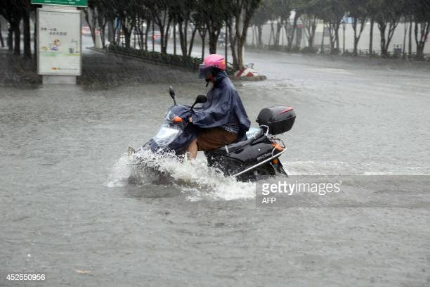 A motorcyclist rides through a flooded area in Jinjiang south China's Fujian province of July 23 2014 as typhoon Matmo makes landfall in China...
