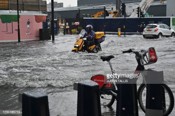 Motorcyclist rides through deep water on a flooded road in The Nine Elms district of London on July 25, 2021 during heavy rain. - Buses and cars were...