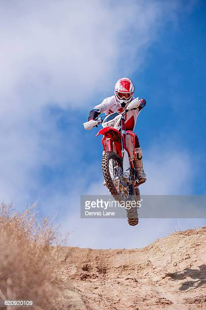 motorcyclist riding dirt bike on hillside - scrambling stock photos and pictures