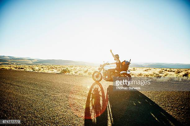 Motorcyclist riding on desert road with arm raised
