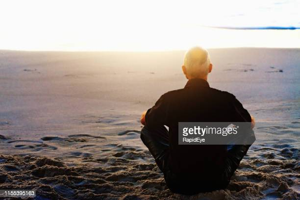 motorcyclist sitting cross-legged, meditating, on beach at sunset - yogi stock pictures, royalty-free photos & images
