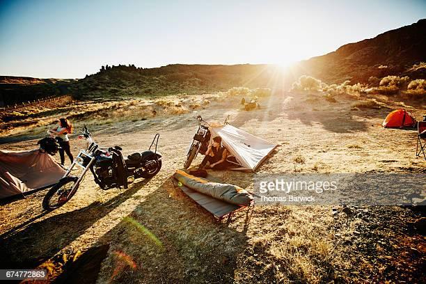 Motorcyclist sitting in tent brushing teeth