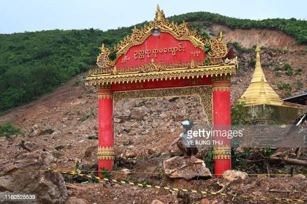 TOPSHOT A motorcyclist squats on a rock in an area affected by a landslide in Paung township Mon state on August 10 2019 The death toll from a...