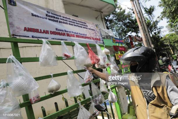 """Motorcyclist takes food that is hung on a wooden shelf """"Pole Sharing Alms"""" at the Muhajidin Mosque. During the coronavirus outbreak, some residents..."""