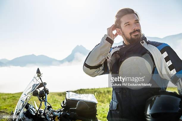 Motorcyclist taking a break on mountain, Tyrol, Austria