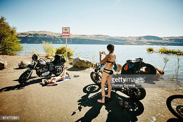 Motorcyclist taking picture of friend lying in sun