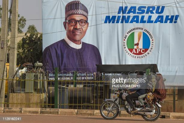 A motorcyclist taxi rides past a campaign poster of candidate of the ruling All Progressives Congress party President Mohammadu Buhari in his native...