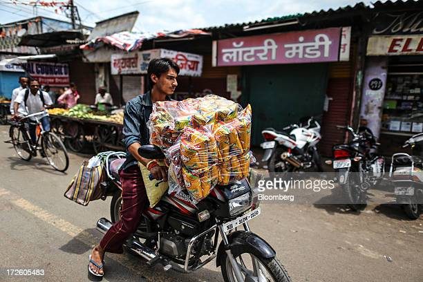 A motorcyclist transports a wholesale pack of potato chips in the Gol Bazaar market in Nagpur India on Sunday June 30 2013 India's services growth...