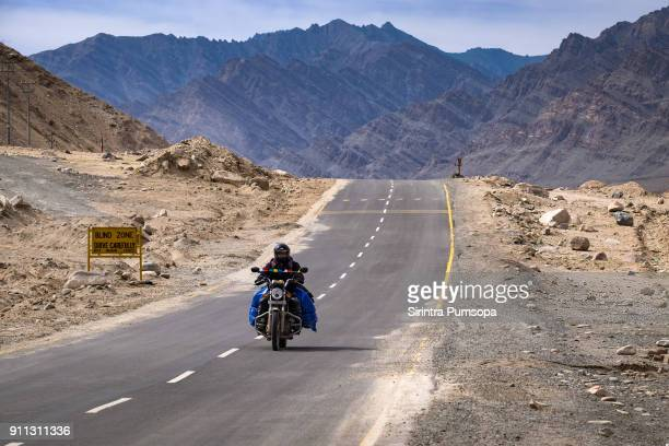 Motorcyclist travels on Highway road in the Himalayas, Leh Ladakh, Jammu and Kashmir, India