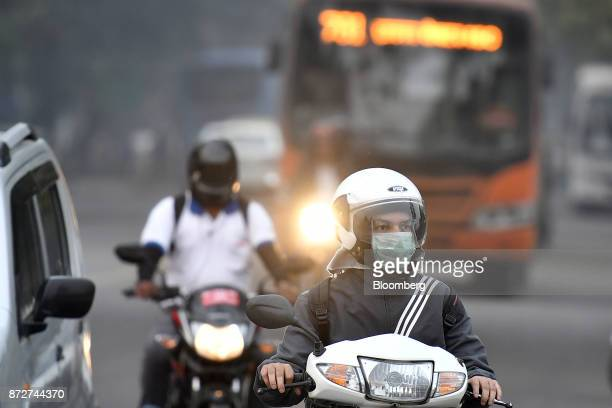 A motorcyclist wearing a face mask drives along a road in New Delhi India on Friday Nov 10 2017 Thick toxic smog enveloped New Delhi forcing schools...