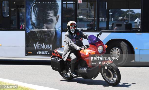 A motorcyclist wearing a mask passes a bus during a charity ride on September 30 2018 in Sydney Australia The Distinguished Gentleman's Ride is an...