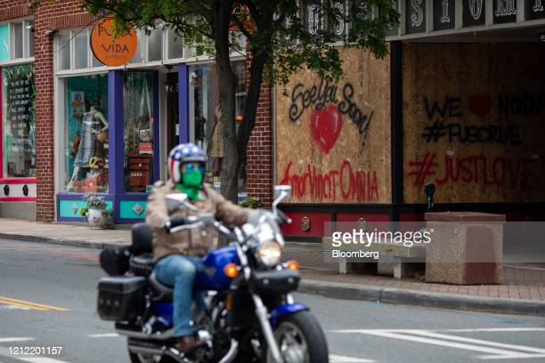 A motorcyclist wearing a protective mask rides past the boarded up windows of a tattoo shop in the NoDa neighborhood of Charlotte North Carolina US...