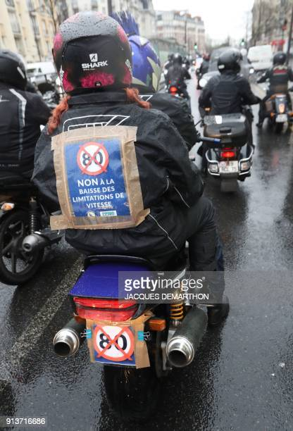 A motorcyclist wears a sign reading 'No to the lowering of the speed limit' as motorcyclists ride together for the French Federation of Angry Bikers'...