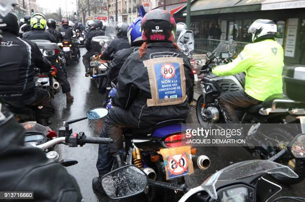 A motorcyclist wears a sign reading 'No to the lowering of the speed limit' asmotorcyclists ride together for the French Federation of Angry Bikers'...