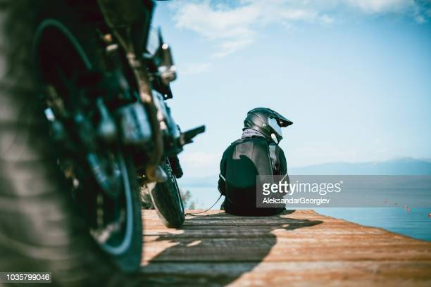 motorcyclist with specialized equipment enjoys the view on the wooden deck - biker jacket stock pictures, royalty-free photos & images