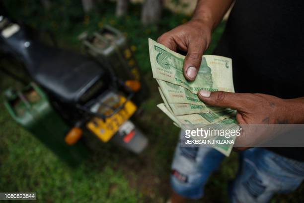 A motorcyclist with two jerry cans attached to his motorbike counts his bond notes at a fuel station on January 11 2019 in Harare Motorists are...