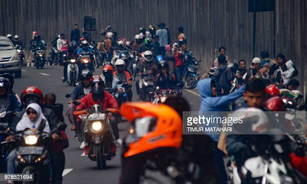 Motorcyclists drive along a road in Bandung as people return from their hometowns following the Eid alFitr festival marking the end of the holy month...
